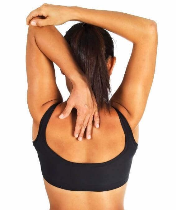 Mulher fazendo alongamento de tríceps