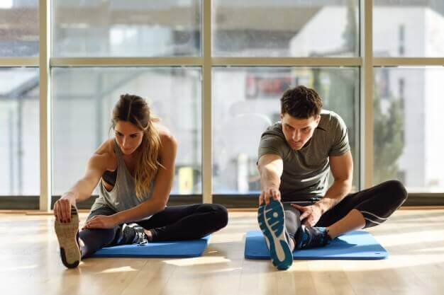 Casal praticando exercícios de alongamento