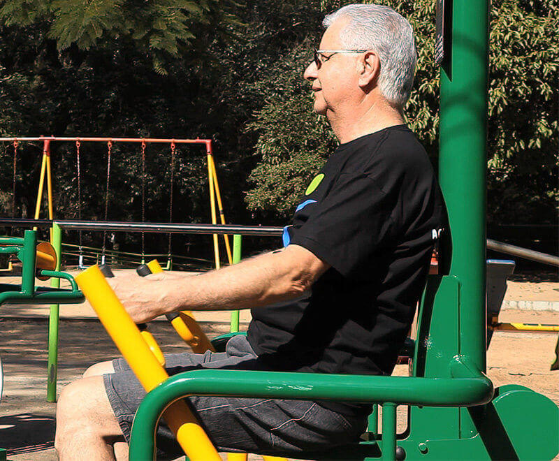 idoso se exercitando em equipamento de academia ao ar livre