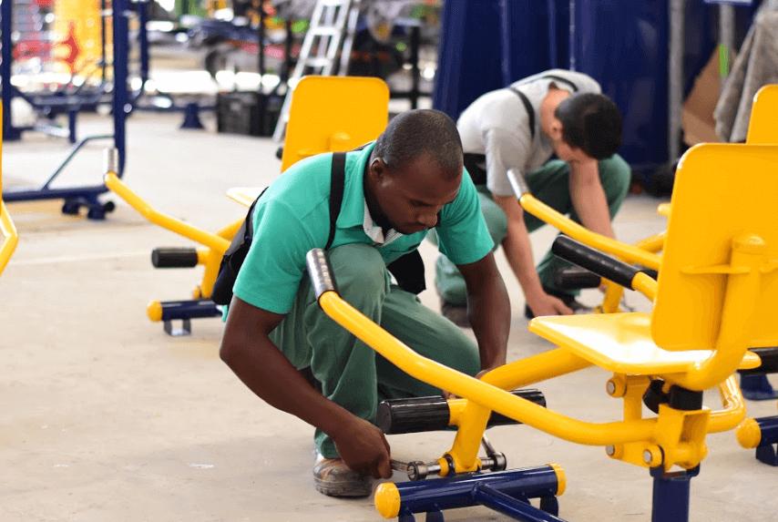 profissional montando equipamento de academia ao ar livre