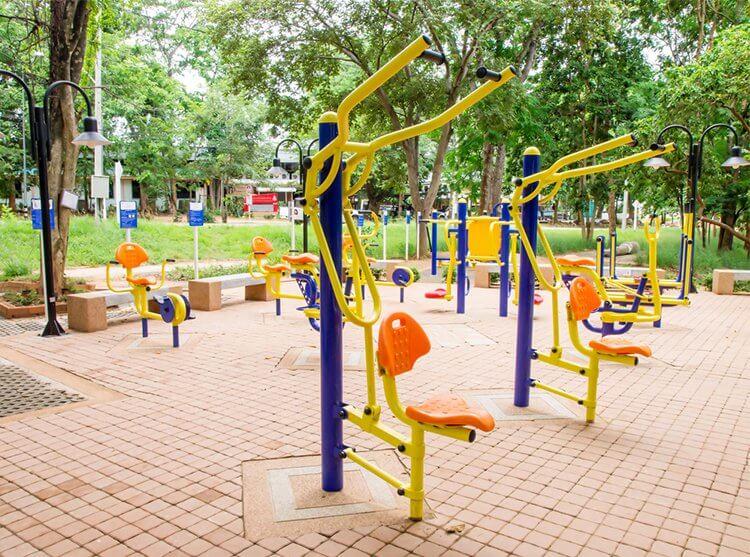 equipamentos de academia ao ar livre em frente a uma praça
