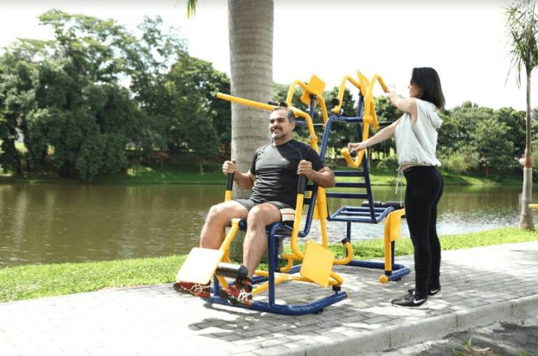 homem e mulher fazendo exercícios em aparelhos de academia ao ar livre