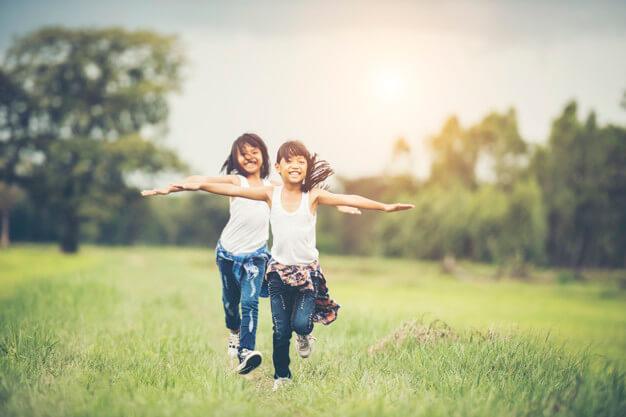 Meninas sorrindo e correndo em um parque infantil