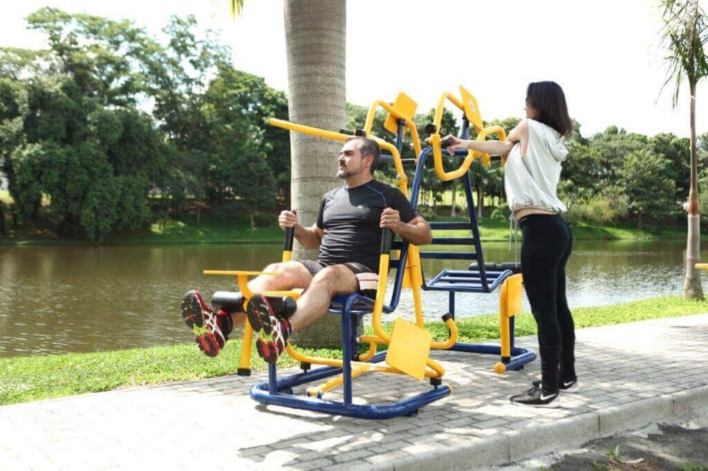 homem e mulher fazendo exercícios em equipamentos de academia ao ar livre
