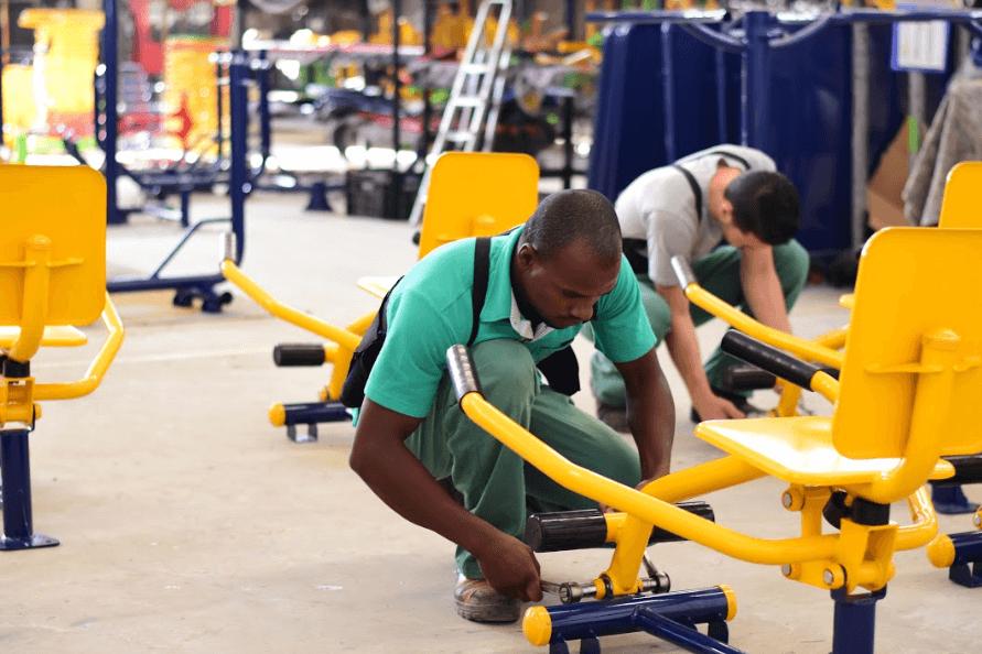profissionais montando equipamentos de academia ao ar livre