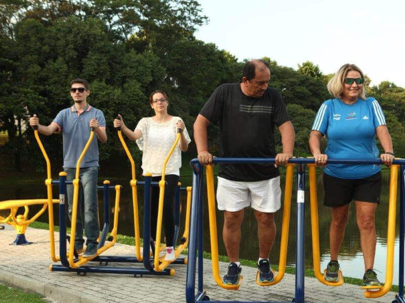 pessoas fazendo exercícios em aparelhos de academia pública