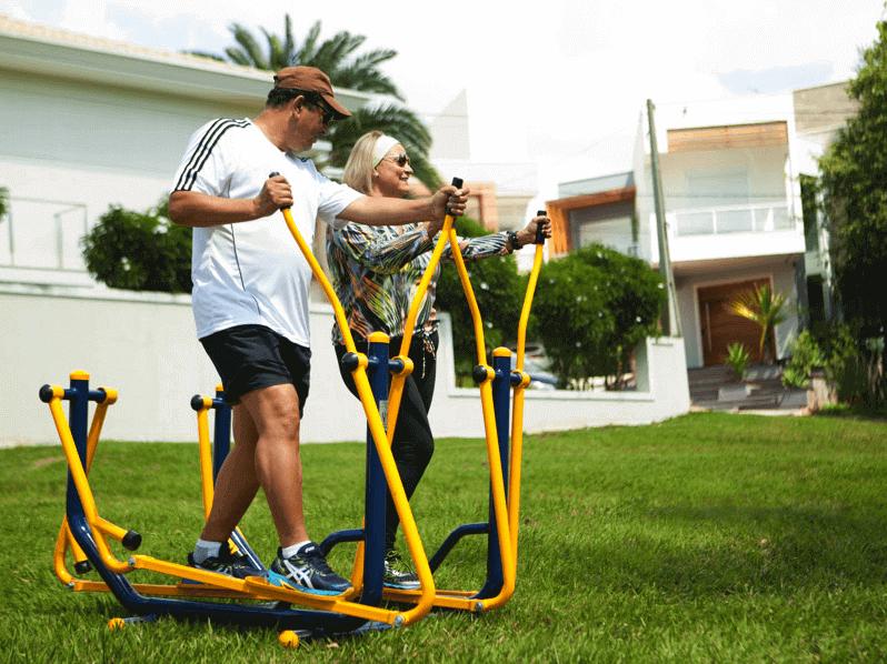 homem e mulher fazendo exercício em equipamentos de academia ao ar livre no gramado