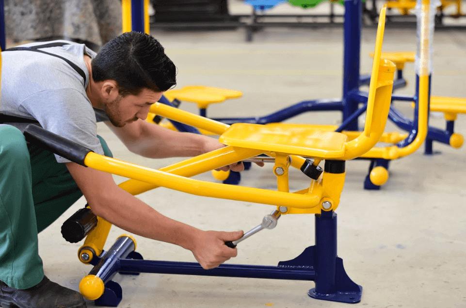 profissional apertando a porca de um equipamento de academia ao ar livre